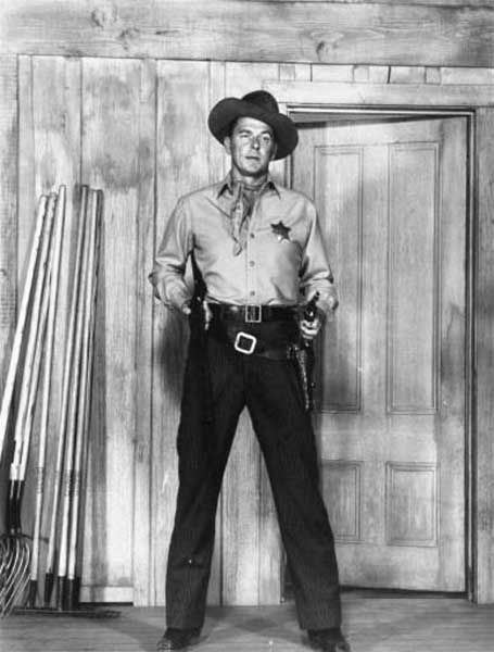 "Actor Ronald Reagan poses, holding a rifle in one hand and a gun in the other, in a scene from the 1953 western film ""Law and Order"", in which Reagan plays a retired U.S. marshall who can't hang up his holster. (AP Photo)"