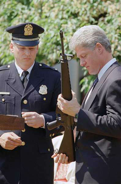 President Bill Clinton holds a Colt AR-15 rifle during a ceremony in the Rose Garden of the White House in Washington, April 25, 1994 where he launched efforts to pass the assault weapons ban. Dayton, Ohio Police Lt. Randy Bean, whose fellow officer Steve Whalen was gunned down with an AR-15 in 1991, looks on at left. (AP Photo/Dennis Cook)