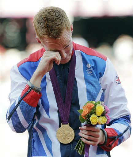 Britain's Greg Rutherford reacts after receiving his gold medal for the men's long jump during the athletics in the Olympic Stadium at the 2012 Summer Olympics, London, Sunday, Aug. 5, 2012. (AP Photo/Luca Bruno)