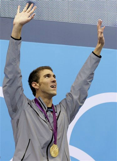 United States' Michael Phelps waves from the podium after winning his 18th gold medal at the Aquatics Centre in the Olympic Park during the 2012 Summer Olympics in London, Saturday, Aug. 4, 2012. (AP Photo/Michael Sohn)