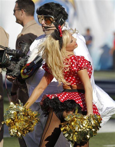 "<div class=""meta ""><span class=""caption-text "">A San Diego Chargers cheerleader in a Halloween costume cheers next to a television cameraman dressed as Elvis during an NFL football game between the Oakland Raiders and the San Diego Chargers Sunday, Nov. 1, 2009 in San Diego.   (AP Photo/ Denis Poroy)</span></div>"