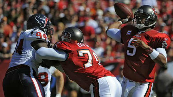 Tampa Bay Buccaneers quarterback Josh Freeman &#40;5&#41; throws a pass as offensive guard Jeremy Zuttah &#40;76&#41; blocks Houston Texans defensive end Antonio Smith &#40;94&#41; during the first quarter of an NFL football game Sunday, Nov. 13, 2011, in Tampa, Fla. &#40;AP Photo&#47;Brian Blanco&#41; <span class=meta>(AP Photo&#47; Brian Blanco)</span>