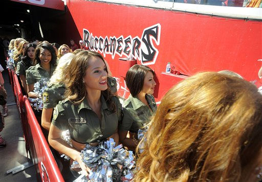 "<div class=""meta ""><span class=""caption-text "">Tampa Bay Buccaneers cheerleaders wearing military-inspired uniforms exit the tunnel and head onto the field at the start of an NFL football game against the Houston Texans Sunday, Oct. 16, 2011, in Tampa, Fla. (AP Photo/Brian Blanco) (AP Photo/ Brian Blanco)</span></div>"