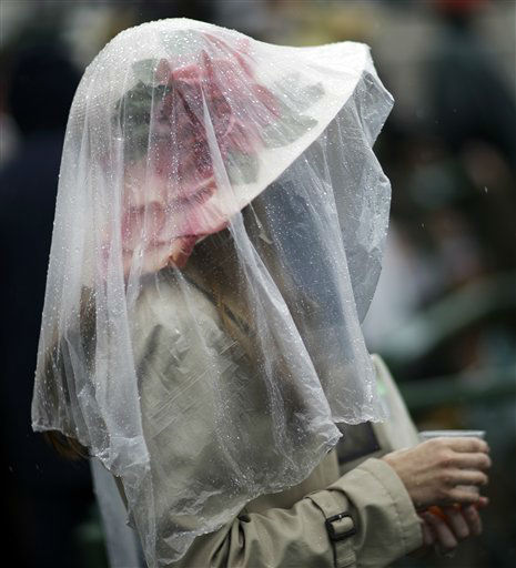 "<div class=""meta ""><span class=""caption-text "">A spectator protects her fancy hat from the rain before the 139th Kentucky Derby at Churchill Downs Saturday, May 4, 2013, in Louisville, Ky.  (AP Photo/ David Goldman)</span></div>"