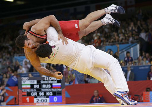 Iran&#39;s Ghasem Gholamreza Rezaei celebrates with his coach after defeating Russia&#39;s Rustam Totrov in their gold medal match in 96-kg Greco-Roman wrestling competition at the 2012 Summer Olympics, Tuesday, Aug. 7, 2012, in London. &#40;AP Photo&#47;Paul Sancya&#41; <span class=meta>(AP Photo&#47; Paul Sancya)</span>