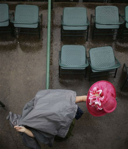 A spectator, covered in a plastic bag, holds her fancy hat while attending the 139th Kentucky Derby at Churchill Downs Saturday, May 4, 2013, in Louisville, Ky.   <span class=meta>(AP Photo&#47; David Goldman)</span>