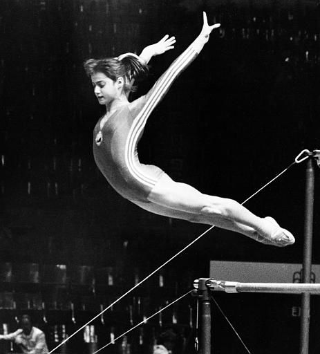 Romanian gymnast Nadia Comaneci performs a perfect jump-off from the uneven bars as she finishes her daily practice at the Montreal gymnasts&#39; training site, July 13, 1976.  The 14-year-old is expected to succeed Russian gymnast Olga Korbut as the darling of the 1976 Summer Games.  &#40;AP Photo&#41; <span class=meta>(AP Photo&#47; Anonymous)</span>