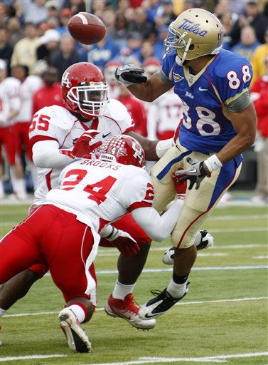 Tulsa wide receiver Bryan Burnham &#40;88&#41; fumbles the ball as he is hit by Houston defensive back Kent Brooks &#40;24&#41; and linebacker Marcus McGraw &#40;55&#41; in the second quarter of an NCAA college football game in Tulsa, Okla., Friday, Nov. 25, 2011. Houston recovered the ball. &#40;AP Photo&#47;Sue Ogrocki&#41; <span class=meta>(AP Photo&#47; Sue Ogrocki)</span>
