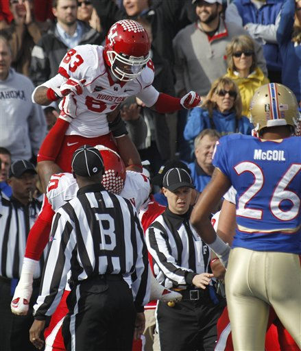 Houston wide receiver Patrick Edwards &#40;83&#41; celebrates a first quarter touchdown against Tulsa with teammate Chris Thompson &#40;70&#41; as Tulsa&#39;s Dexter McCoil looks on at right, during an NCAA college football game in Tulsa, Okla., Friday, Nov. 25, 2011. &#40;AP Photo&#47;Sue Ogrocki&#41; <span class=meta>(AP Photo&#47; Sue Ogrocki)</span>