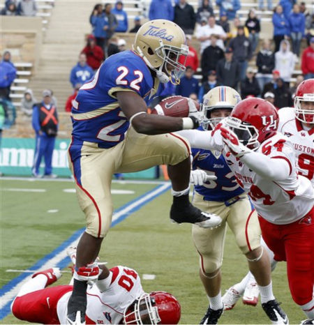 Tulsa tailback Trey Watts &#40;22&#41; jumps over Houston defensive lineman Zeke Riser &#40;90&#41; as linebacker Everett Daniels &#40;54&#41; moves in for the tackle in the fourth quarter of an NCAA college football game in Tulsa, Okla., Friday, Nov. 25, 2011. &#40;AP Photo&#47;Sue Ogrocki&#41; <span class=meta>(AP Photo&#47; Sue Ogrocki)</span>