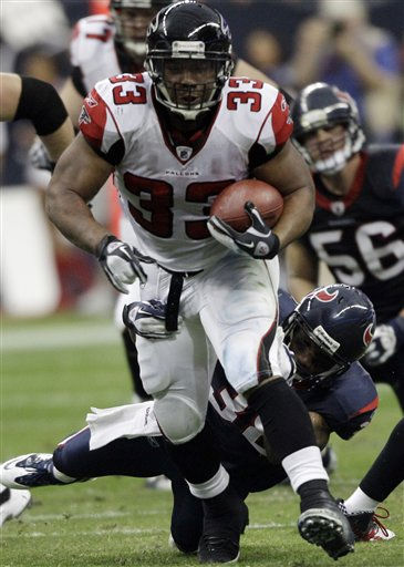 Atlanta Falcons running back Michael Turner &#40;33&#41; evades Houston Texans free safety Danieal Manning &#40;38&#41; in the second quarter of an NFL football game on Sunday, Dec. 4, 2011, in Houston. &#40;AP Photo&#47;David J. Phillip&#41; <span class=meta>(AP Photo&#47; David J. Phillip)</span>