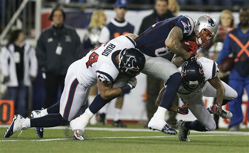 New England Patriots tight end Aaron Hernandez is tackled by Houston Texans linebacker Barrett Ruud &#40;54&#41; and Johnathan Joseph, right, during the first half of an AFC divisional playoff NFL football game in Foxborough, Mass., Sunday, Jan. 13, 2013.   <span class=meta>(AP Photo&#47; Elise Amendola)</span>