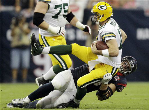 Houston Texans defensive end J.J. Watt, bottom, sacks Green Bay Packers quarterback Aaron Rodgers &#40;12&#41; in the first quarter of an NFL football game, Sunday, Oct. 14, 2012, in Houston. &#40;AP Photo&#47;Patric Schneider&#41; <span class=meta>(AP Photo&#47; Patric Schneider)</span>