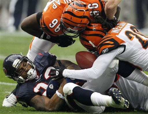 Houston Texans running back Arian Foster &#40;23&#41; almost fumbles the ball after being tackled by Cincinnati Bengals free safety Reggie Nelson &#40;20&#41; and  Carlos Dunlap &#40;96&#41; during the first quarter of an NFL wild card playoff football game Saturday, Jan. 7, 2012, in Houston. &#40;AP Photo&#47;Eric Gay&#41; <span class=meta>(AP Photo&#47; Eric Gay)</span>