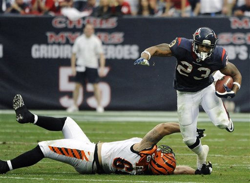 Cincinnati Bengals defensive end Jonathan Fanene &#40;68&#41; can&#39;t get a good hold on Houston Texans running back Arian Foster &#40;23&#41; during the second quarter of an NFL wild card playoff football game Saturday, Jan. 7, 2012, in Houston. &#40;AP Photo&#47;Dave Einsel&#41; <span class=meta>(AP Photo&#47; Dave Einsel)</span>