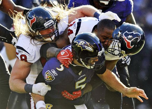 Houston Texans defensive end Antonio Smith, right, loses his helmet as he and teammate outside linebacker Brooks Reed, left, tackle Baltimore Ravens quarterback Joe Flacco &#40;5&#41; during the first half of an NFL divisional playoff football game in Baltimore, Sunday, Jan. 15, 2012. &#40;AP Photo&#47;Gail Burton&#41; <span class=meta>(AP Photo&#47; Gail Burton)</span>