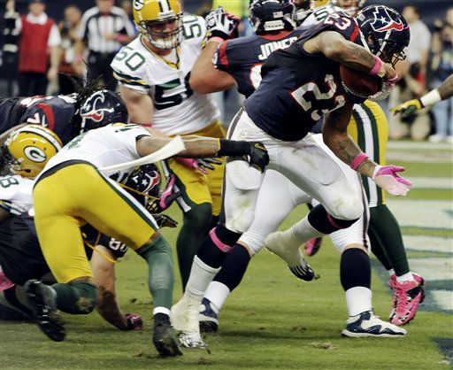 Houston Texans running back Arian Foster &#40;23&#41; drags Green Bay Packers defender Charles Woodson, left, as he crosses into the end zone to score a touchdown in the second quarter of an NFL football game, Sunday, Oct. 14, 2012, in Houston. &#40;AP Photo&#47;Dave Einsel&#41; <span class=meta>(AP Photo&#47; Dave Einsel)</span>