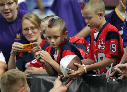 JJ Watt signs a ball for Texans fans before the preseason opener in Minnesota   <span class=meta>(AP photo)</span>