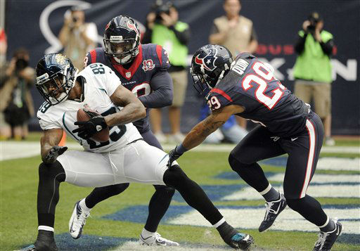 Jacksonville Jaguars tight end Marcedes Lewis &#40;89&#41; lands in the end zone for a touchdown despite the efforts of Houston Texans&#39; Danieal Manning &#40;38&#41; and Glover Quin &#40;29&#41; during the first quarter of an NFL football game on Sunday, Nov. 18, 2012, in Houston.   <span class=meta>(AP Photo&#47; Dave Einsel)</span>