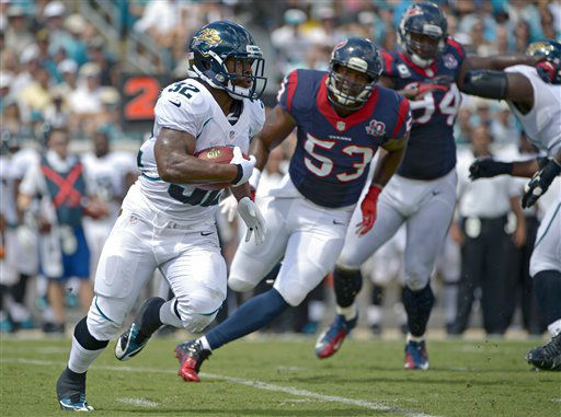 Jacksonville Jaguars running back Maurice Jones-Drew &#40;32&#41; makes a move to get around Houston Texans inside linebacker Bradie James &#40;53&#41; and defensive end Antonio Smith &#40;94&#41; during the first half of an NFL football game on Sunday, Sept. 16, 2012, in Jacksonville, Fla. &#40;AP Photo&#47;Phelan M. Ebenhack&#41; <span class=meta>(AP Photo&#47; Phelan M. Ebenhack)</span>