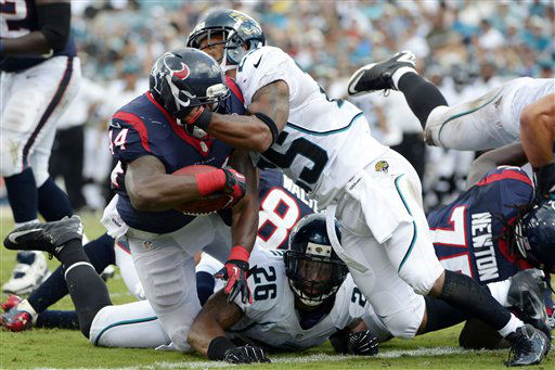 Houston Texans running back Ben Tate, left, scores a touchdown against pressure from Jacksonville Jaguars free safety Dawan Landry &#40;26&#41; and strong safety Dwight Lowery, right, during the first half of an NFL football game, Sunday, Sept. 16, 2012, in Jacksonville, Fla. &#40;AP Photo&#47;Phelan M. Ebenhack&#41; <span class=meta>(AP Photo&#47; Phelan M. Ebenhack)</span>