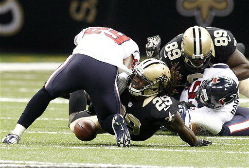 New Orleans Saints running back Chris Ivory, foreground bottom, fumbles the football on a hit by Houston Texans defensive back Glover Quin, foreground top,in the first half of an NFL preseason football game in New Orleans, Saturday, Aug. 25, 2012. &#40;AP Photo&#47;Bill Haber&#41; <span class=meta>(AP Photo&#47; Bill Haber)</span>