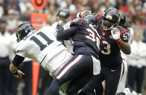 Jacksonville Jaguars quarterback Blaine Gabbert &#40;11&#41; is grabbed by Houston Texans Danieal Manning &#40;38&#41; and Bradie James &#40;53&#41;during the first quarter of an NFL football game Sunday, Nov. 18, 2012, in Houston. Gabbert left the game with an elbow contusion.   <span class=meta>(AP Photo&#47; Patric Schneider)</span>
