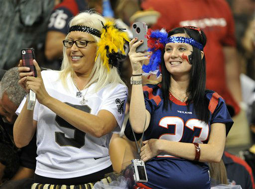 A New Orleans Saints fan and a Houston Texans take pictures in the first half of an NFL preseason football game against the Houston Texans in New Orleans, Saturday, Aug. 25, 2012. &#40;AP Photo&#47;Bill Haber&#41; <span class=meta>(AP Photo&#47; Bill Haber)</span>