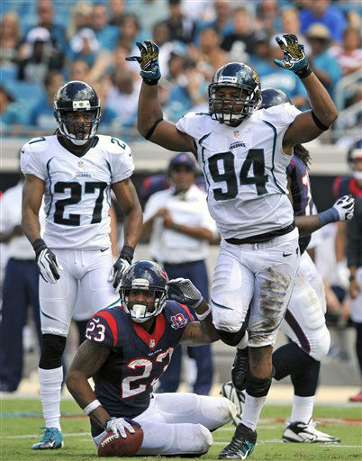 Jacksonville Jaguars defensive end Jeremy Mincey &#40;94&#41; celebrates a stop on Houston Texans running back Arian Foster &#40;23&#41; as Jacksonville Jaguars cornerback Rashean Mathis &#40;27&#41; looks on during the first half an NFL football game on Sunday, Sept. 16, 2012, in Jacksonville, Fla. &#40;AP Photo&#47;Stephen Morton&#41; <span class=meta>(AP Photo&#47; Stephen Morton)</span>