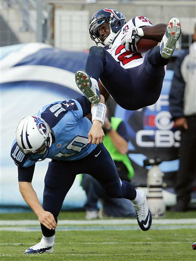 Tennessee Titans quarterback Jake Locker &#40;10&#41; tackles Houston Texans inside linebacker Tim Dobbins &#40;52&#41; after Dobbins intercepted a pass by Locker in the second quarter of an NFL football game on Sunday, Dec. 2, 2012, in Nashville, Tenn. &#40;AP Photo&#47;Joe Howell&#41; <span class=meta>(AP Photo&#47; Joe Howell)</span>