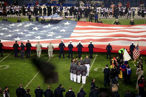 Military personnel hold a giant flag as the West Point &#34;Knight Caps&#34; Glee Club, foreground, sings the national anthem as part of the NFL&#39;s Salute to Service campaign on Veterans Day before an NFL football game between the Chicago Bears and Houston Texans, Sunday, Nov. 11, 2012, in Chicago. &#40;AP Photo&#47;Kiichiro Sato&#41; <span class=meta>(Photo&#47;Kiichiro Sato)</span>
