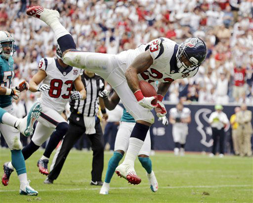 Houston Texans running back Arian Foster &#40;23&#41; leaps into the end zone for a touchdown against the Miami Dolphins in the second quarter of an NFL football game, Sunday, Sept. 9, 2012, in Houston. &#40;AP Photo&#47;Eric Gay&#41; <span class=meta>(AP Photo&#47; Eric Gay)</span>