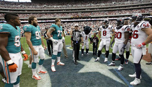 Referee Don King, center, flips the coin before an NFL football game between the Miami Dolphins and Houston Texans Sunday, Sept. 9, 2012, in Houston. The Texans won 30-10. &#40;AP Photo&#47;David J. Phillip&#41; <span class=meta>(AP Photo&#47; David J. Phillip)</span>