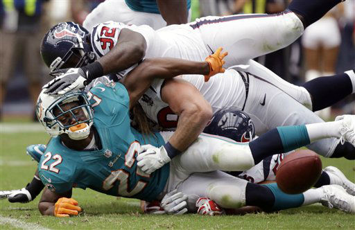 Miami Dolphins running back Reggie Bush &#40;22&#41; fumbles the ball after being tackled by Houston Texans&#39; Earl Mitchell &#40;92&#41; and Brooks Reed, center, in the first quarter of an NFL football game on Sunday, Sept. 9, 2012, in Houston. &#40;AP Photo&#47;Eric Gay&#41; <span class=meta>(AP Photo&#47; Eric Gay)</span>