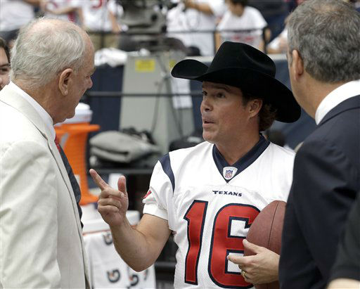 Singer Clay Walker, center, talks with Houston Texans owner Bob McNair, left, and his son Cal McNair, right, before an NFL football game against the Miami Dolphins Sunday, Sept. 9, 2012, in Houston. &#40;AP Photo&#47;David J. Phillip&#41; <span class=meta>(AP Photo&#47; David J. Phillip)</span>