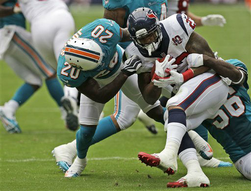 Houston Texans running back Arian Foster, center, and Miami Dolphins  Reshad Jones &#40;20&#41; and  Kevin Burnett &#40;56&#41; in the first quarter of an NFL football game Sunday, Sept. 9, 2012, in Houston. &#40;AP Photo&#47;David J. Phillip&#41; <span class=meta>(AP Photo&#47; David J. Phillip)</span>