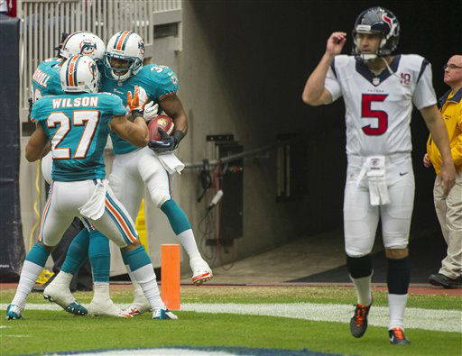 Miami Dolphins&#39; Jimmy Wilson &#40;27&#41; Nolan Carroll, left, and Marcus Thigpen, right, celebrate Thigpen&#39;s punt return for a touchdown as Houston Texans punter Donnie Jones &#40;5&#41; walks off during an NFL football game, Sunday, Sept. 9, 2012, in Houston. The Texans beat the Dolphins 30-10. &#40;AP Photo&#47;Dave Einsel&#41; <span class=meta>(AP Photo&#47; Dave Einsel)</span>