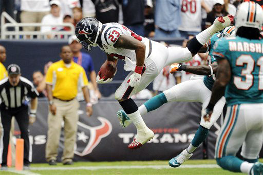Houston Texans running back Arian Foster &#40;23&#41; leaps into the end zone for a touchdown as Miami Dolphins defensive back Chris Clemons, right, tries to tackle him in the second quarter of an NFL football game, Sunday, Sept. 9, 2012, in Houston. &#40;AP Photo&#47;Dave Einsel&#41; <span class=meta>(AP Photo&#47; Dave Einsel)</span>