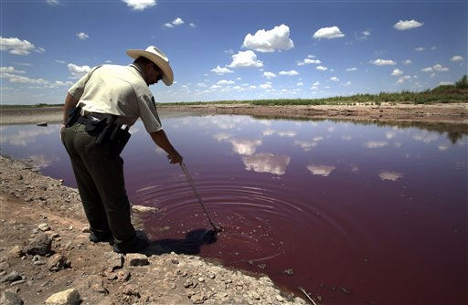 Texas State Park police officer Thomas Bigham reaches down into what remains of O.C. Fisher Lake Wednesday, Aug. 3, 2011, in San Angelo, Texas. A bacteria called Chromatiaceae has turned the 1-to-2 acres of lake water remaining the color red. A combination of the long periods of 100 plus degree days and the lack of rain in the drought -stricken region has dried up the lake that once spanned over 5400 acres. &#40;AP Photo&#47;Tony Gutierrez&#41; <span class=meta>(AP Photo&#47; Tony Gutierrez)</span>