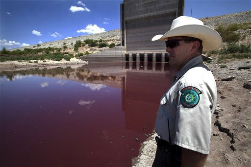 Texas State Park police officer Thomas Bigham stands by the dam as he looks out at a small patch of red-tinted water in what remains of O.C. Fisher Lake Wednesday, Aug. 3, 2011, in San Angelo, Texas. A bacteria called Chromatiaceae has turned the 1-to-2 acres of lake water remaining the color red. A combination of the long periods of 100 plus degree days and the lack of rain in the drought -stricken region has dried up the lake that once spanned over 5400 acres.  &#40;AP Photo&#47;Tony Gutierrez&#41; <span class=meta>(AP Photo&#47; Tony Gutierrez)</span>