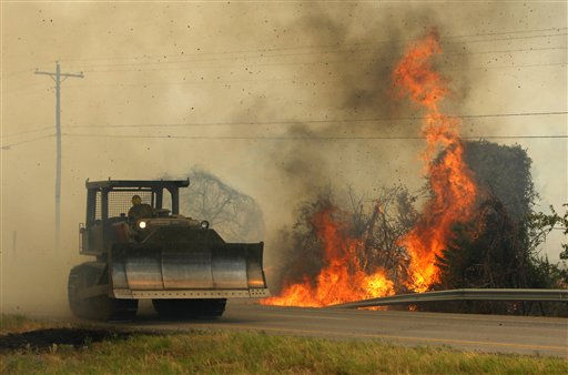 "<div class=""meta ""><span class=""caption-text "">A large wildfire burns along Highway 71 near Smithville, Texas  as a bulldozer from the Texas Forest Service rumbles by Monday, Sep. 5, 2011.  A roaring wildfire raced unchecked Monday through rain-starved farm and ranchland in Texas, destroying nearly 500 homes during a rapid advance fanned in part by howling winds from the remnants of Tropical Storm Lee.  (AP Photo/Erich Schlegel) (AP Photo/ Erich Schlegel)</span></div>"