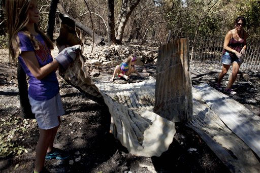 Friends and family members return Tuesday afternoon Sept. 6, 2011, to their homes in Austin, Texas,  Steiner Ranch community after wildfires in the area were contained. Erin Clawson, left, rumages with Shianne and Colleen Galasso through the remains of their friends&#39; cabin.  &#40;AP Photo&#47;Danielle Villasana&#47;The Daily Texan&#41; <span class=meta>(AP Photo&#47; Danielle Villasana)</span>