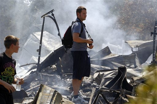 "<div class=""meta ""><span class=""caption-text "">Brothers Ben, left, and Nathan Clements survey their fire-destroyed home, Tuesday, Sept. 6, 2011, in Bastrop, Texas. The Clements lost their home to fires Monday. (AP Photo/Eric Gay) (AP Photo/ Eric Gay)</span></div>"