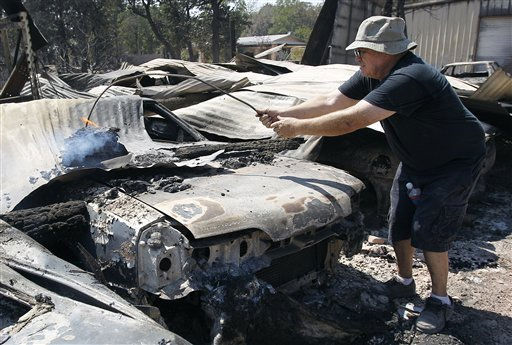 Car collector John Chapman fishes a burning log off one of his vehicles as he surveys the losses at his home, Tuesday, Sept. 6, 2011, in Bastrop, Texas. Chapman lost more than 170 cars to the wildfires. More than 1,000 homes have been destroyed in at least 57 wildfires across rain-starved Texas, most of them in one devastating blaze near Austin that is still raging out of control, officials said Tuesday.   &#40;AP Photo&#47;Eric Gay&#41; <span class=meta>(AP Photo&#47; Eric Gay)</span>