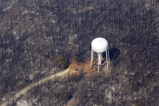 FILE - In this Sept. 7, 2011 file photo, n area destroyed by wildfire surrounds a water tower, Wednesday, Sept. 7, 2011, in Bastrop, Texas. The fire has destroyed more than 600 homes and blackened about 45 square miles in and around Bastrop. As the soggy Northeast tries to dry out from flooding and Texas prays for rain that doesn&#39;t come, it seems like an ideal match of oversupply and unquenchable demand. It isn?t.  &#40;AP Photo&#47;Eric Gay, File&#41; <span class=meta>(AP Photo&#47; Eric Gay)</span>