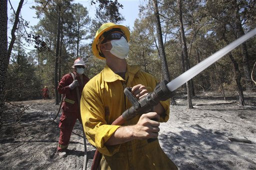 Volunteer fireman Ryan Mills douses hot spots with water on a wildfire near Bastrop, Texas, Friday, Sept. 9, 2011. Texas is suffering its worst wildfire outbreak in state history. The Bastrop-area fire has been the largest of nearly 190 wildfires the forest service says erupted this week, leaving nearly 1,700 homes statewide in charred ruins, killing four people and forcing thousands of people to evacuate.   &#40;AP Photo&#47;LM Otero&#41; <span class=meta>(AP Photo&#47; LM Otero)</span>