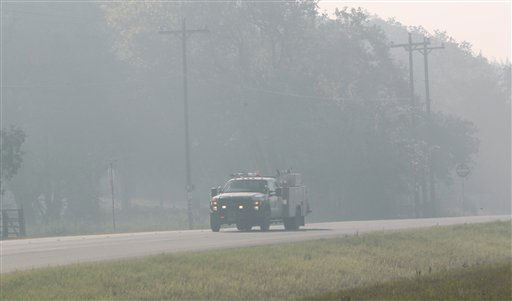 A truck drives through hanging smoke near Bastrop, Texas, Friday, Sept. 9, 2011.  Texas is suffering its worst wildfire outbreak in state history. The Bastrop-area fire has been the largest of nearly 190 wildfires the forest service says erupted this week, leaving nearly 1,700 homes statewide in charred ruins, killing four people and forcing thousands of people to evacuate.   &#40;AP Photo&#47;LM Otero&#41; <span class=meta>(AP Photo&#47; LM Otero)</span>