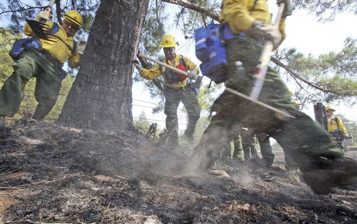 A fresh team of firefighters just arrived from the Sequoia National Forest in California climb over a barbed wire fence on their way to put out hot spots on the fire near Bastrop, Texas, Friday, Sept. 9, 2011.  &#40;AP Photo&#47;LM Otero&#41; <span class=meta>(AP Photo&#47; LM Otero)</span>