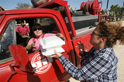 Robin Hamilton, right, of the Bosque Resort Restaurant in Whitney, Texas provides meals to firefighter Kelli Jones of the West Shore Volunteer Fire Department during a break battling wildfires Friday Sept.9, 2011 near Whitney, Texas. Over 500 acres of land burned including six homes. &#40;AP Photo&#47;Waco Tribune-Herald, Duane A. Laverty&#41; <span class=meta>(AP Photo&#47; Duane A. Laverty)</span>