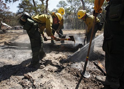 A fire fighting crew from the Lassen National Forest in Calif., clean up hot spots after the destructive wildfire in Bastrop, Texas, Sept. 10, 2011.  Officials in Texas say fire crews are making progress fighting a massive Texas wildfire but concerns about hotspots are keeping thousands of residents in the Bastrop area from returning home.  &#40;AP Photo&#47;Eric Schlegel - POOL&#41; <span class=meta>(AP Photo&#47; ERICH SCHLEGEL)</span>